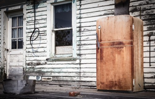 a rusty refrigerator on the porch